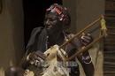 uomo Pokot che suona strumento tradizionale